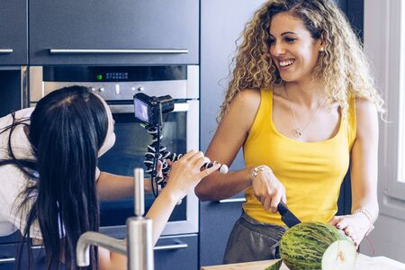 Young blonde girl cutting a melon with a knife in the kitchen, while another girl records her with a camera Stock fotó