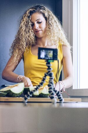 Young blonde girl cutting a melon with a knife in the kitchen, while recording with a camera