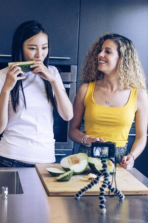 Asian young girl tasting a piece of melon, another smiling young woman is cutting the melon while they are recording with a camera
