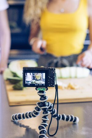 Young blonde girl cutting a melon with a knife in the kitchen, while recording with a camera. Selective focus