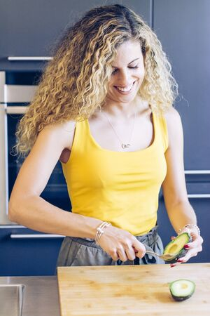 Smiling young girl peeling an avocado with a spoon in the kitchen