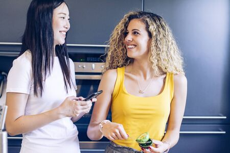Smiling young girl peeling an avocado with a spoon in the kitchen while another girl is checking her mobile phone