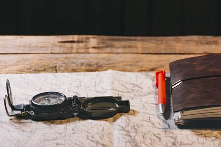 Compass, maps and other objects for a trip in the mountains or country. Wooden background. Adventure, freedom, planning and leave your comfort zone concept