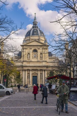 Paris, France - November 7, 2019: Chapel of the Sorbonne University. People on the street in front of the church. A man walking with a bicycle Éditoriale