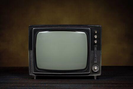 Alter tragbarer Fernseher. Holztisch und brauner Hintergrund. Konzept der Obsoleszenz, Modernisierung oder technologischen Revolution Standard-Bild