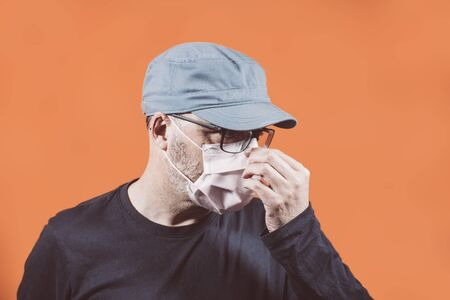 Portrait of man in cap putting on a face mask with an orange background. Concepts of contagion, influenza or coronavirus
