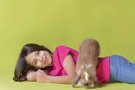 Little girl playing with her pet rabbit lying on the floor with the rabbit running down her back, in a studio, with vivid colors. Selective focus on the girl