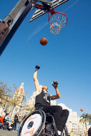 Valencia, Spain. February 15, 2020 - Adaptive sports day. An adaptive basketball player throwing the ball into the basket on the prepared court in the town hall square