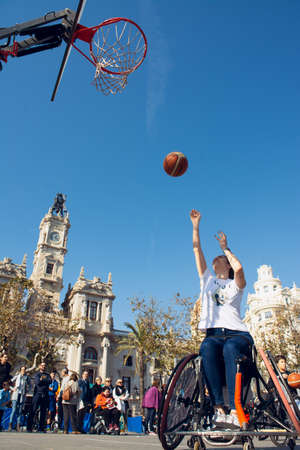 Valencia, Spain. February 15, 2020 - Adaptive sports day. An adaptive basketball player throwing the ball into the basket on the prepared court in the town hall square Redactioneel