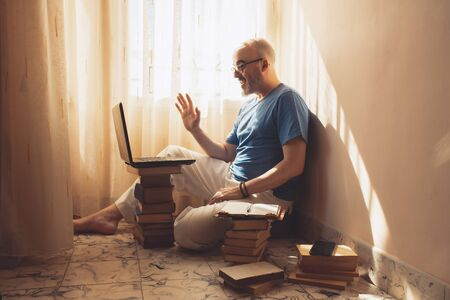 Middle-aged man on a video conference at home with his laptop on a pile of books like a desk. Concept work from home, home office or telecommuting