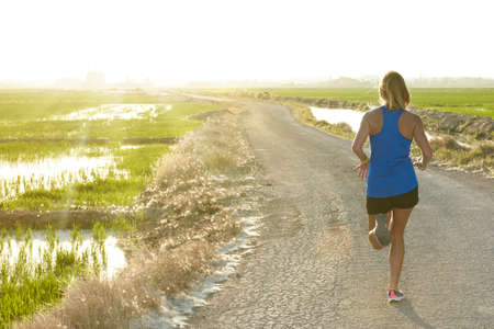 Sunset backlight of a young athlete girl in blue shirt running down a path next to a rice field