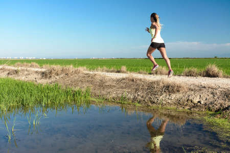 A young athlete girl in a yellow shirt running down a path between rice fields, with her reflection in the paddy water
