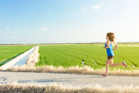 A young athlete girl in a blue shirt running down a path between rice fields, with her reflection in the paddy water