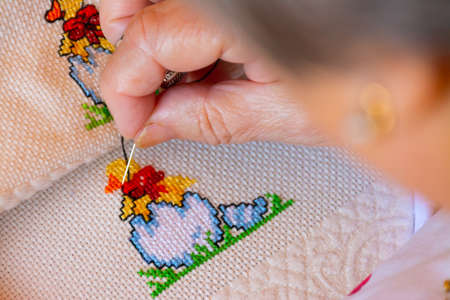 Woman creating black details to a colorful cross stitch design. Concepts of manual work or work at home.