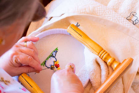 A woman cuts the thread at the back of a cross stitch pattern. Concepts of manual work or work at home.