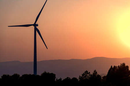 Windmill tower with mountains and orange sky of sunset or sunrise in the background and trees in the foreground. With copy space. Clean energy, climate change and ecology concepts. 免版税图像