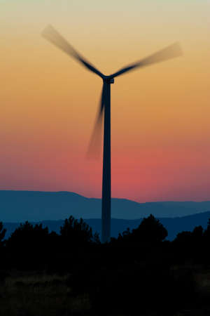 Windmill tower backlight with blades in movement, and yellow and orange sky and mountains in the background Concepts of clean energy, climate change and ecology