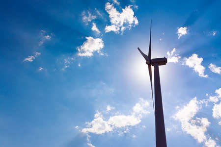 Backlight of a windmill tower with the sun behind the engine and cloudy blue sky with beams of sunlight. Clean energy, climate change and ecology concepts 免版税图像