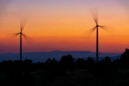 Two windmill towers in backlight with blades in movement, and yellow and orange sky and mountains in the background Concepts of clean energy, climate change and ecology