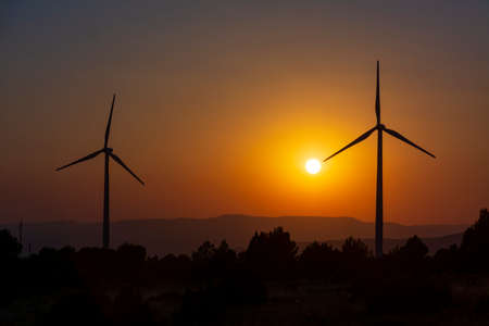 Two windmill towers with mountains and orange sky of sunset or sunrise in the background and trees in the foreground. With copy space. Clean energy, climate change and ecology concepts.