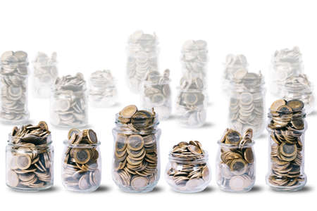 Some glass jars full of euro coins, other glass jars out of focus, on white background with copy space