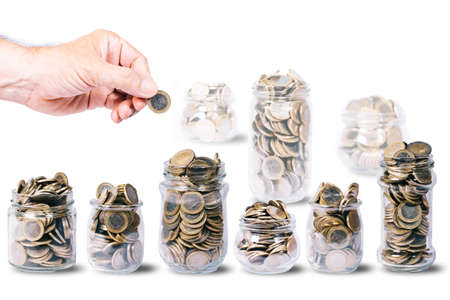 Male hand with one euro coin over several glass jars full of euro coins, other glass jars out of focus, on white background with copy space