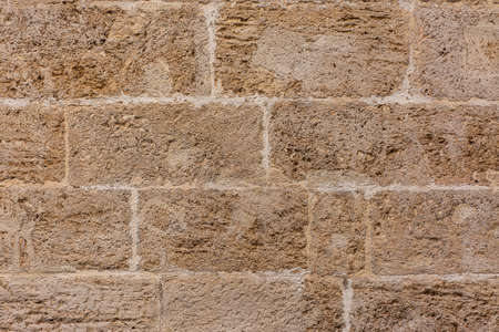 Old textured yellow stone block wall creating a pattern. Background for designs or advertising
