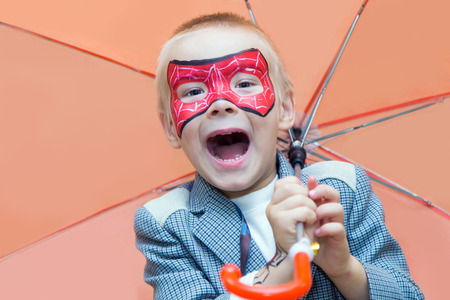 Excited caucasian boy with a spiderman mask on his face smiles at camera while holding an umbrella. Stock Photo