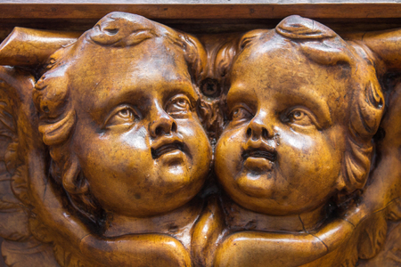 Two faces wooden cherubim angels facing each other and looking upwards