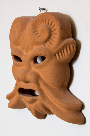 Ocher and brown terracotta ancient mask hanging on white background