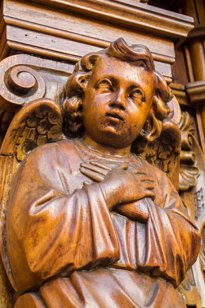 A wooden angel with his coated hands decorating a column