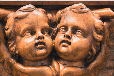 Wooden statue of angels facing each other and looking upwards