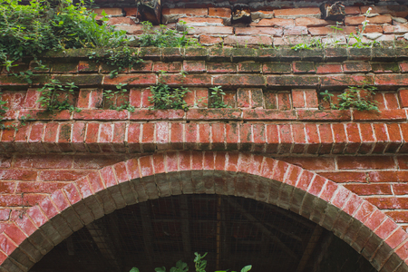 Red brick arch with grass that supporting roof in Crespi dAdda Фото со стока