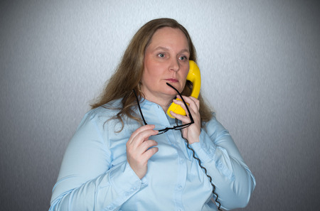 intellectually: Businesswoman on phone calls and is thoughtfully chewing on her glasses Stock Photo