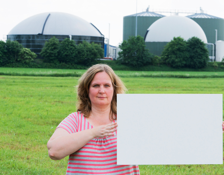 bioenergy: Woman holding a sign in front of a biogas plant Stock Photo