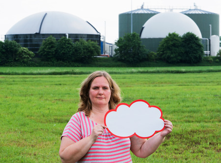 methane: Woman holding a sign in front of a biogas plant Stock Photo