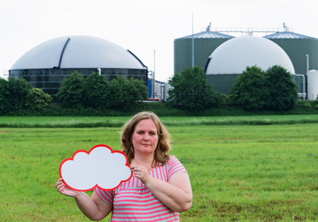 Woman holding a sign in front of a biogas plant Stock Photo