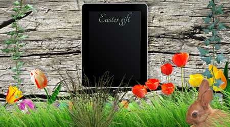 Tablet on wooden board with Easter Gift