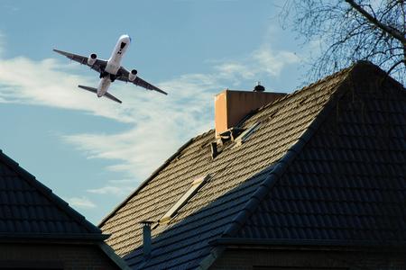 Vliegtuig bij vertrek over een woonwijk