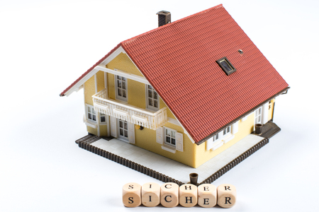 Sure, German text for safe, word in letters on cube in front of a model house Stock Photo