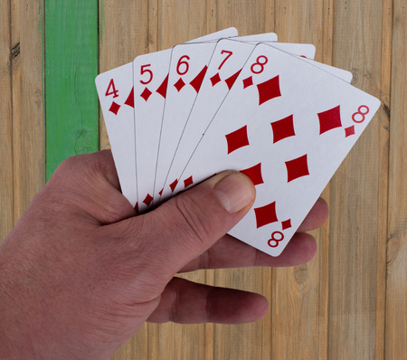 Poker game playing cards Straight flush in the hand Stock Photo