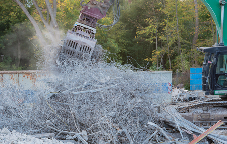 Demolition excavator rips off a building
