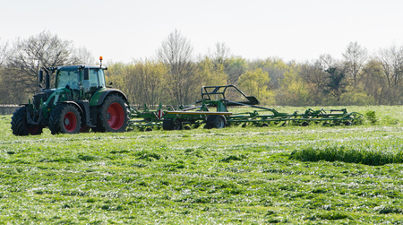 Agricultural tractor returns grass for the haymaking Standard-Bild - 122393303