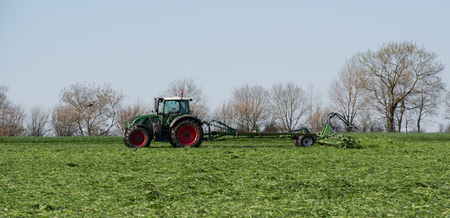 Agricultural tractor returns grass for the haymaking Standard-Bild - 122393305