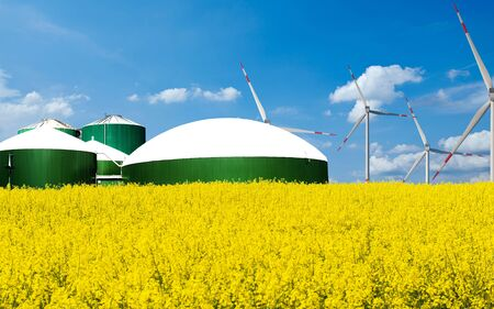 L'usine de biogaz se tient derrière un champ arable avec le ciel bleu