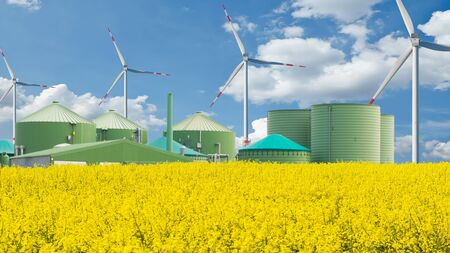 Biogas plant stands behind a arable field with blue sky