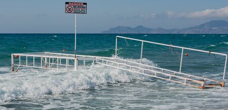 Broken bathing place with waves overflowing in storm in the Mediterranean, on Kos Greece