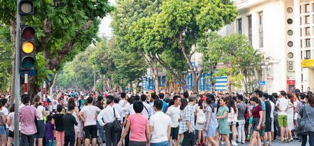 Vietnamese people and crowds on a large street in Hanoi, Vietnam