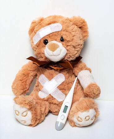 Sick Teddy Bear with bandage and plaster as cut Imagens