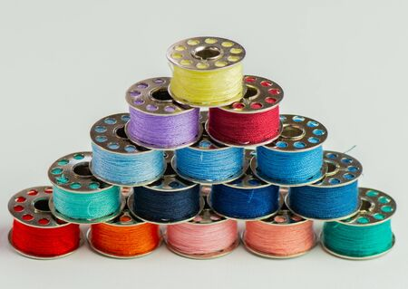 Sewing thread rolls in various colors at a tailor shop against a white background